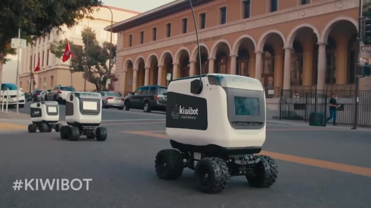 Three kiwibots out for food delivery with one ahead of the other two close enough to see the print on the side of the bot