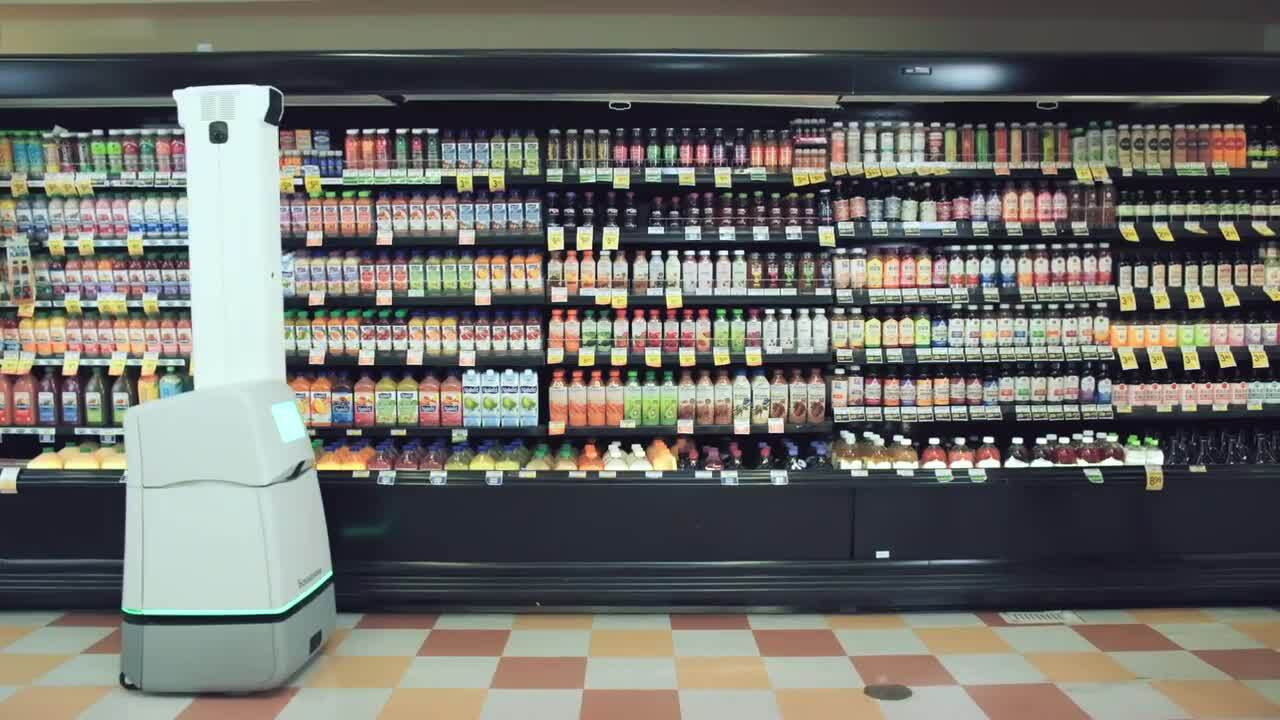 Wide view of a juice section in a grocery store with a robot in front of the shelves