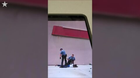 Police forcibly arrest a person on a Kansas City sidewalk