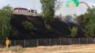 Firefighters put down grass fire alongside Highway 180 at start of commute