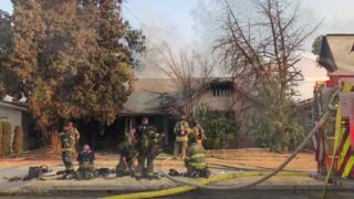 Firefighters at the scene of a house fire in Fresno, CA