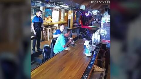 Man tries to finish drink at bar as police escort him out