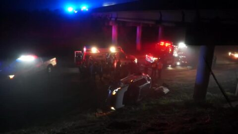 SUV rolls over interstate bridge, down hill but all 5 people escape serious injury