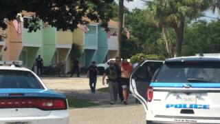 Man in handcuffs led from apartments on Yaupon Drive