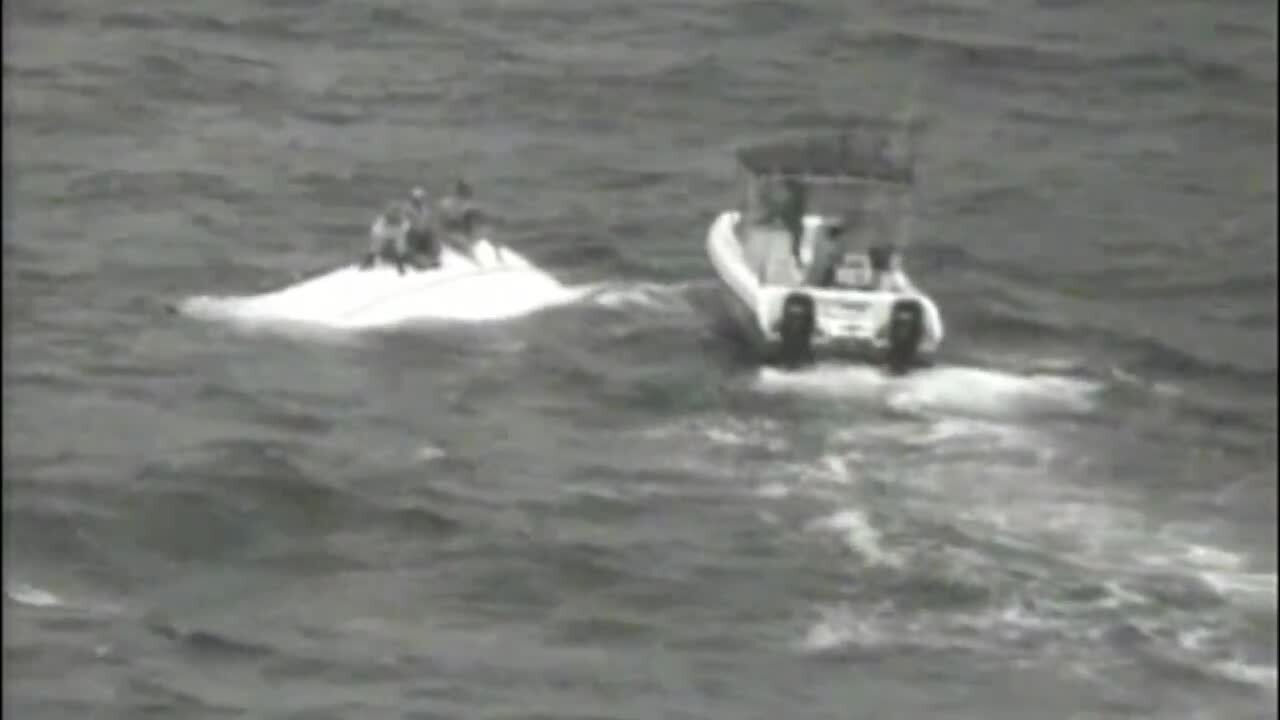 Watch as trio sitting on top of capsized boat is saved by a good Samaritan