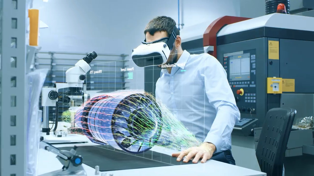 Man standing in a research lab using VR goggles to vizualize a piece of machinery
