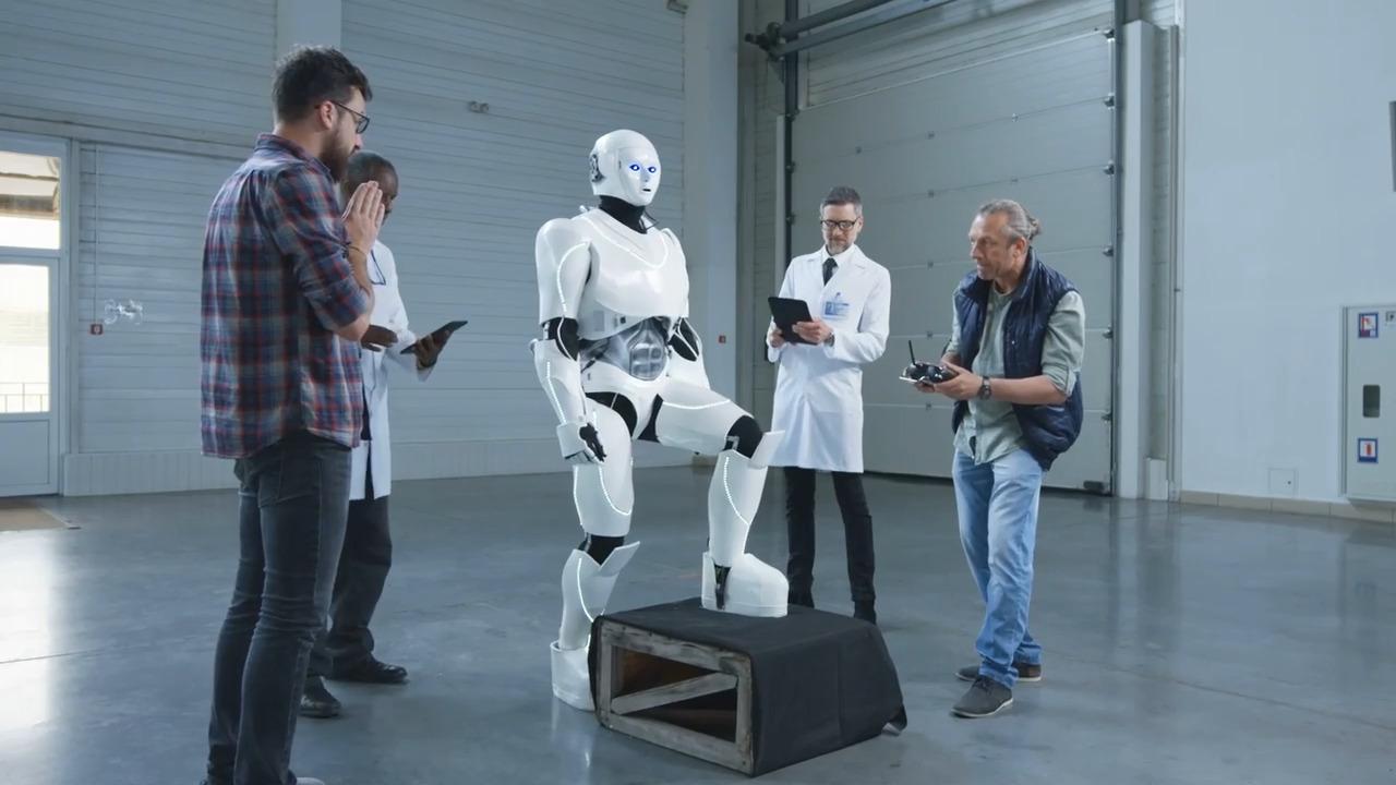 Cuatro ingenieros trabajando en un robot de apariencia humana