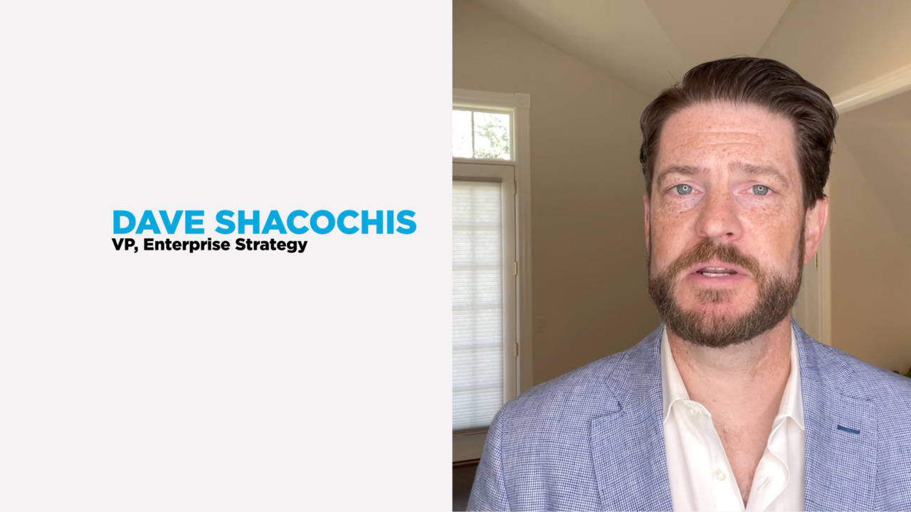 Close up of businessman Dave Shacochis standing next to white background with text of his name & job title