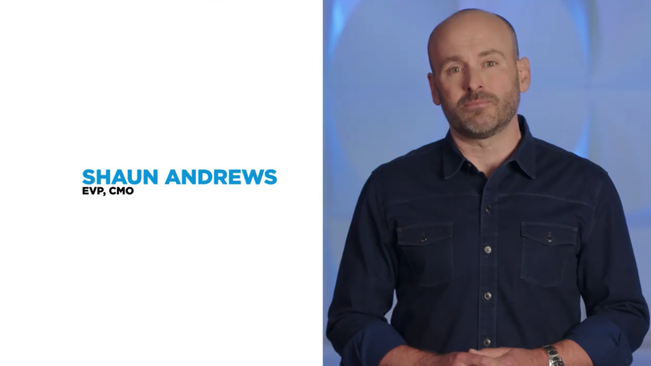 Close up of businessman Shaun Andrews standing next to white background with text of his name & job title