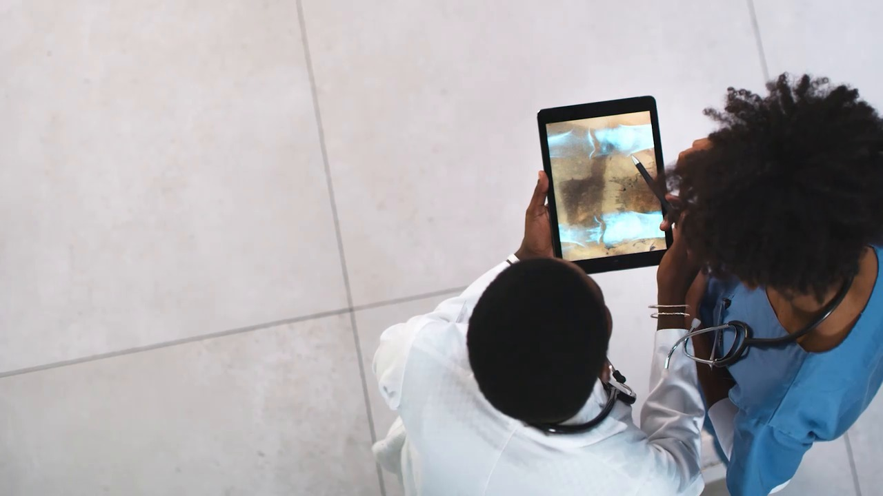 Overhead view of two medical professionals looking at an x-ray on a tablet device