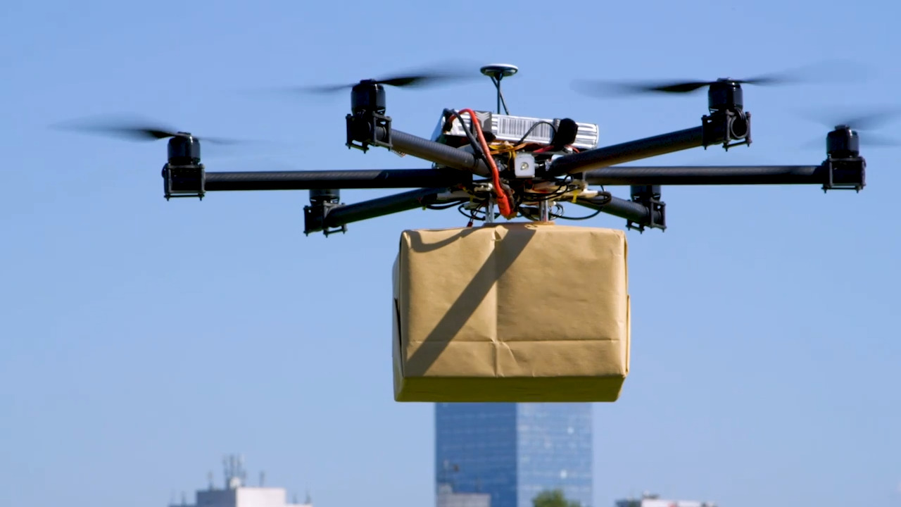 Close up of a drone in the sky carrying a parcel above a city skyline