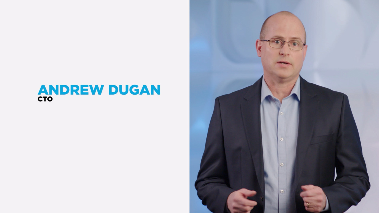 Close up of businessman Andrew Dugan standing next to white background with text of his name & job title