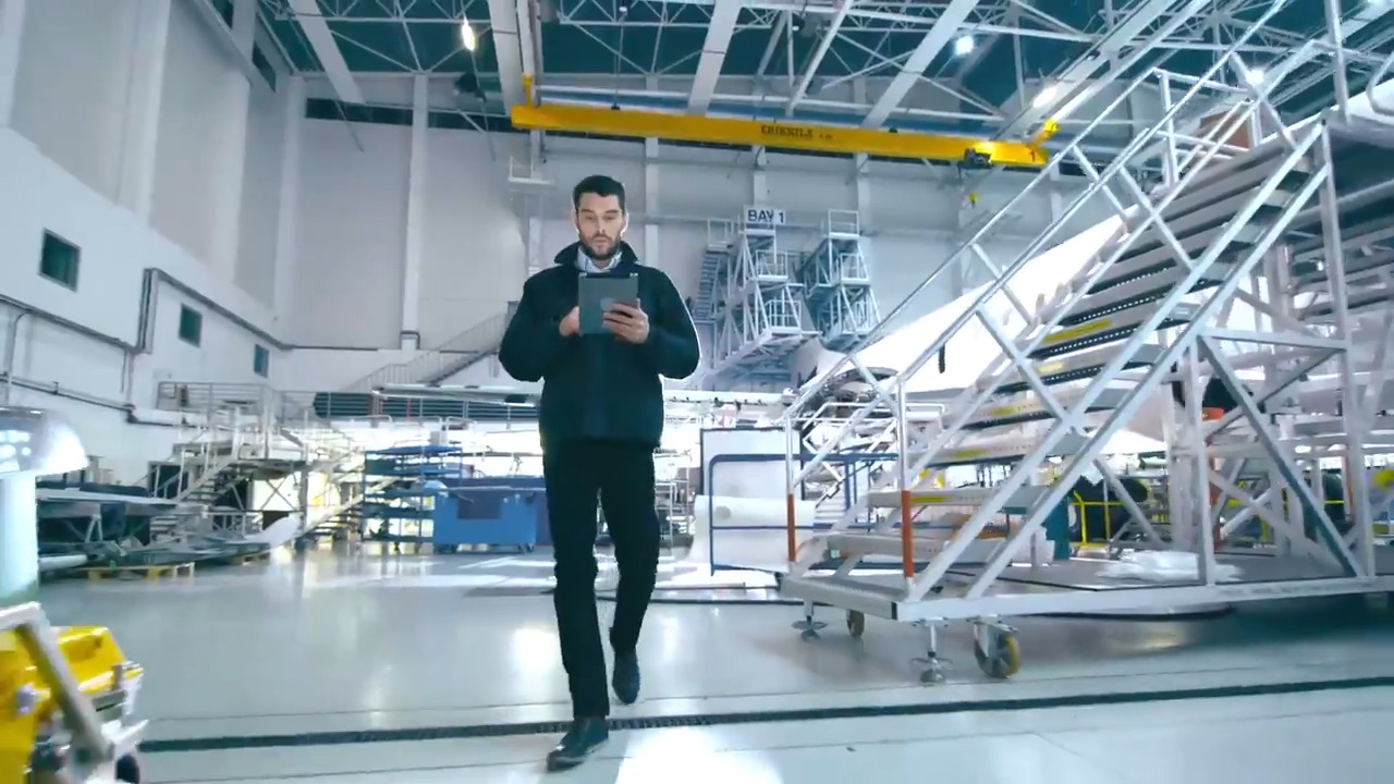 An engineer walking through a large hanger looking at a tablet