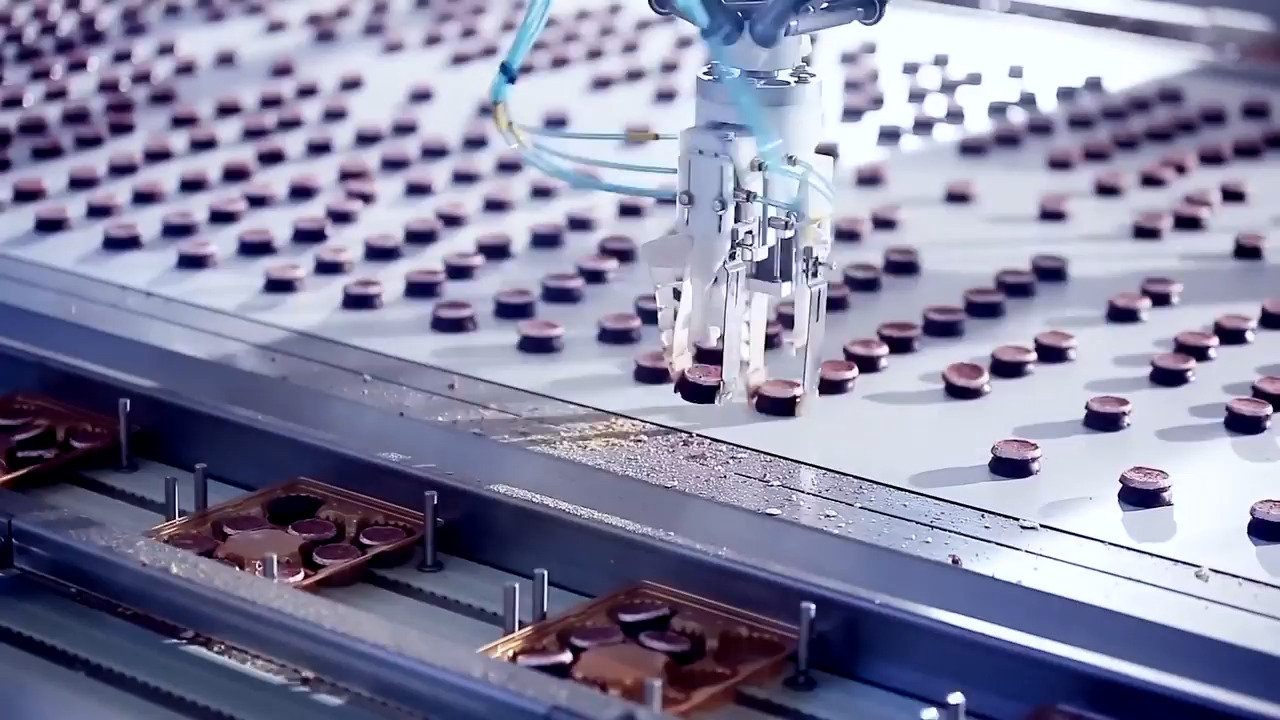 Close up of an assembly line using a robot arm to move items off into their packaging