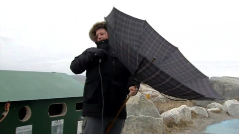 WEATHER NETWORK REPORTER'S UMBRELLA IS NO MATCH FOR THE WIND AT PEGGY'S COVE, NOVA SCOTIA