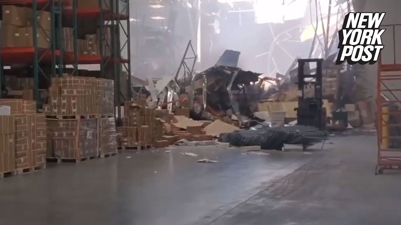 Fighter jet crashes, tears hole in warehouse wall