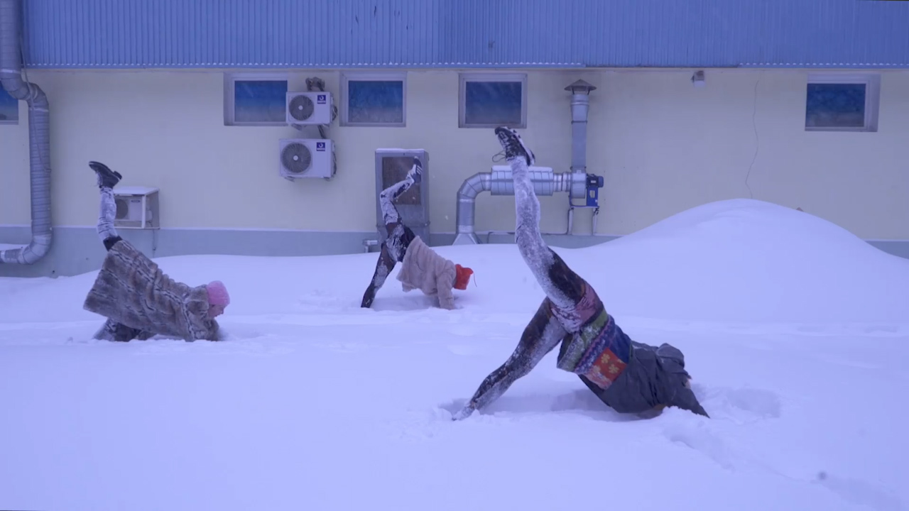 Women from artist group Beyond practice yoga in snowy Moscow