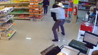 Man in cowboy hat wrestles gun away from man holding up butcher's shop