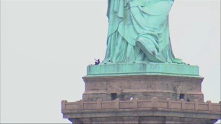 Person climbs base of Statue of Liberty