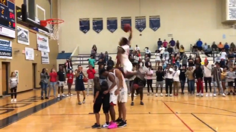 High school basketball player throws down over four people