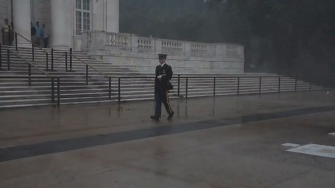 Soldier lays flag during downpour at Arlington National Cemetery