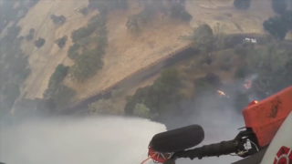 Helicopter uses water drop to control California wildfire