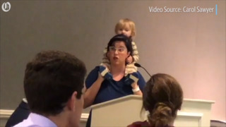 Multi-tasking mom wrangles restless toddler while delivering flawless speech
