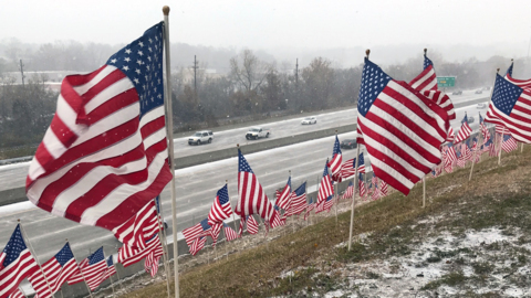 Snow blows over Interstate 35 in Merriam near a Veterans Day flag display