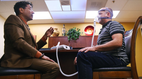 He sleeps with a machine that pumps air into his lungs. Oh, the joys of sleep apnea