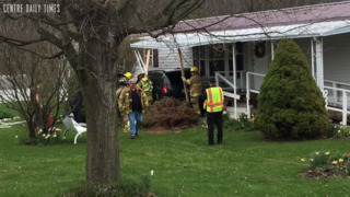 Police and fire crews remove an elderly driver who crashed into a residence