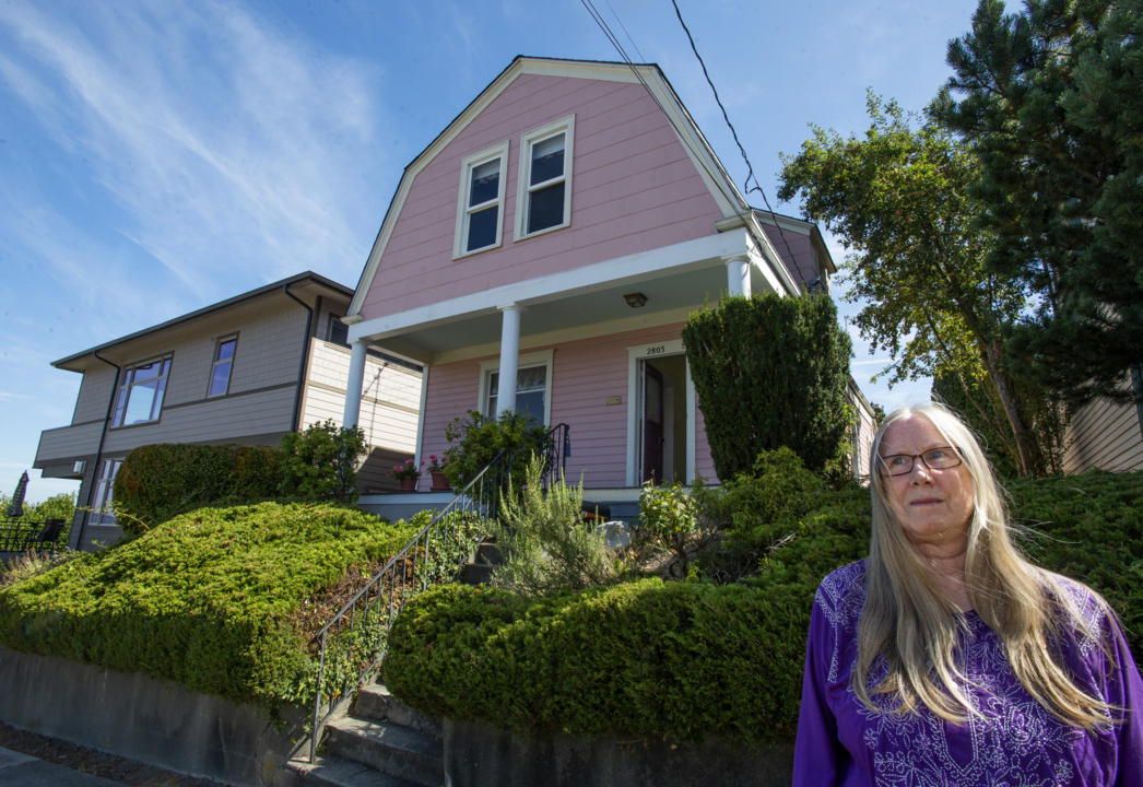 Historic home owner wants off city list as her home is overwhelmed by modern neighbors