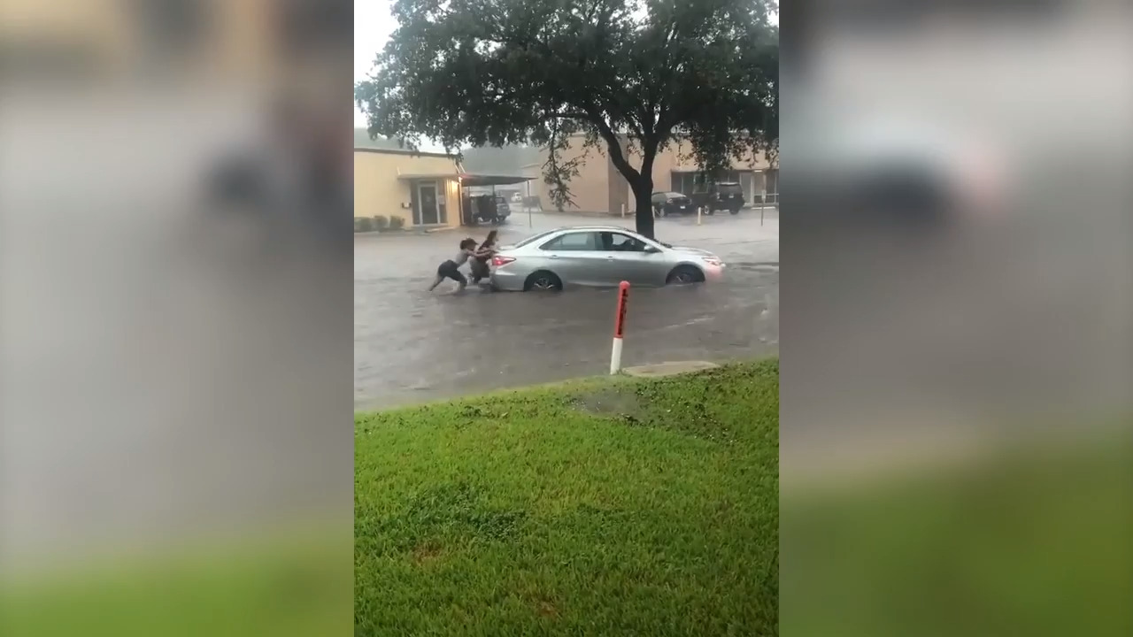 Women push car through floodwaters as Imelda bears down on Houston, video shows