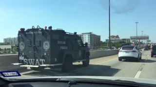 Armored police vehicles rush to a Dallas Home Depot where two officers were shot