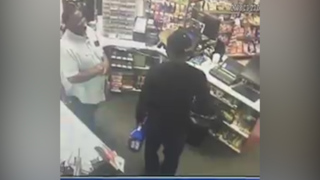 Gas station employee smiles as he gets robbed