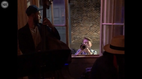 Young musician joins jazz session from outside window of New Orleans club