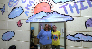 """Volunteers use paint, creativity to transform school bathrooms and inspire students to """"bloom where you are planted."""""""