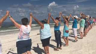 'Hands Along the Water' demonstration against red tide brings hundreds to Anna Maria Island