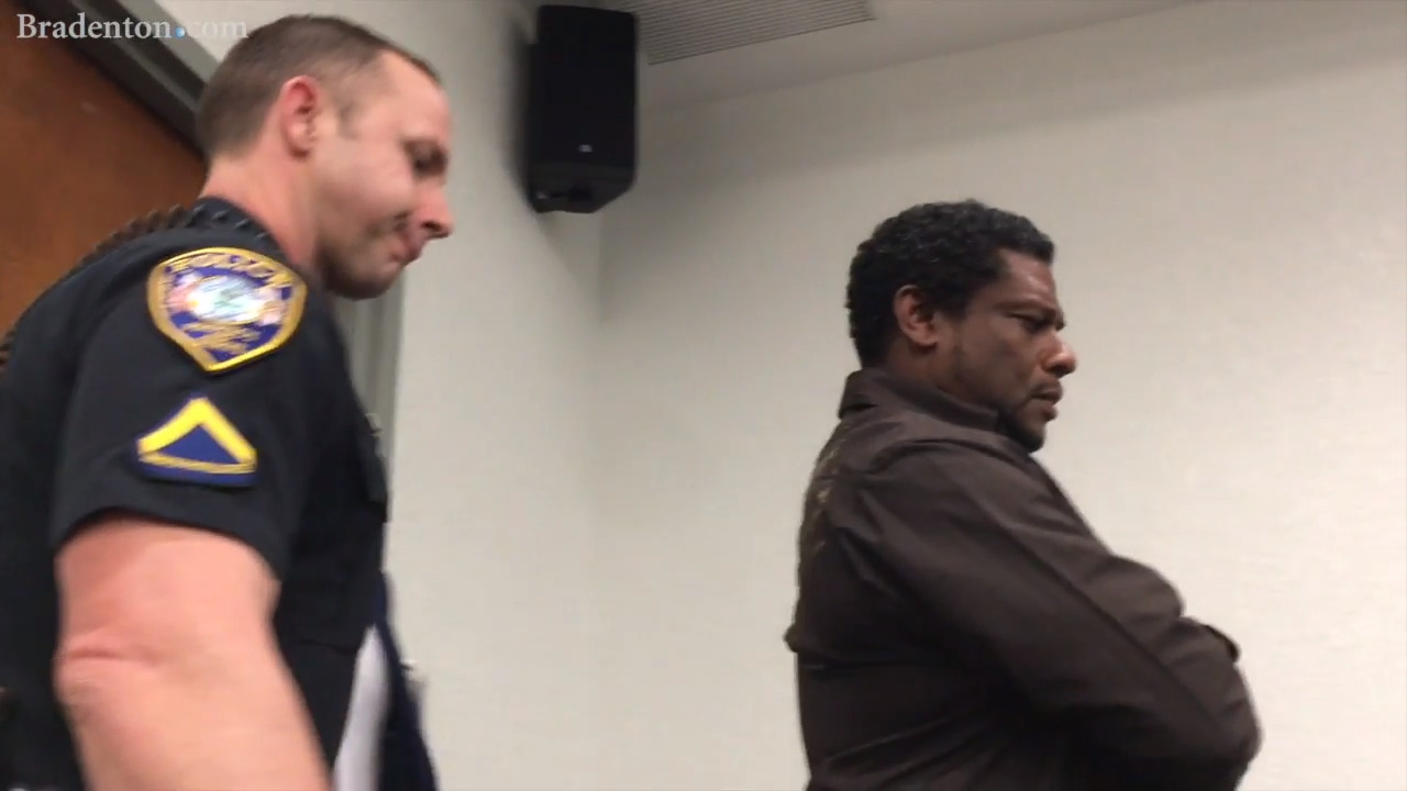 A man stood in silence at the Manatee school board meeting. Police made him leave
