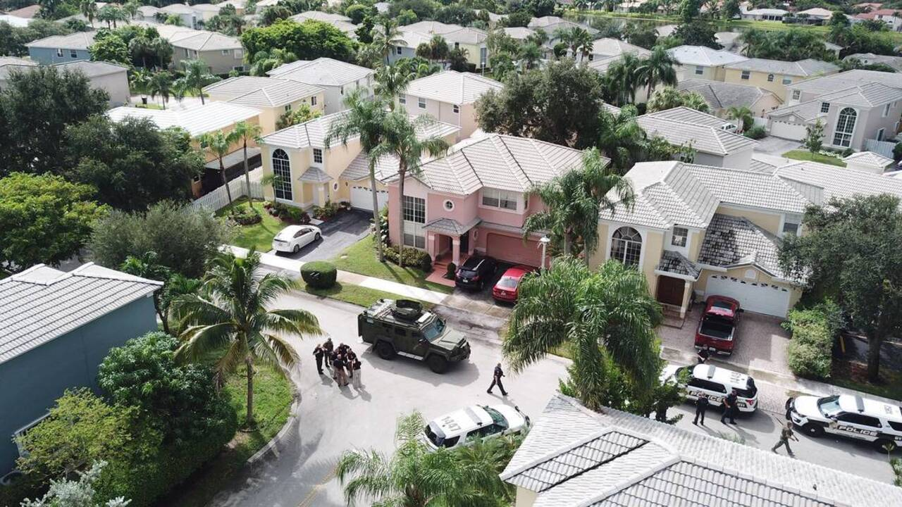 A chaotic Coconut Creek scene: Two dead, cop shot, dog killed, rifles found