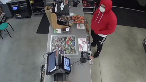 Man wearing red hoodie and mask robs convenience store