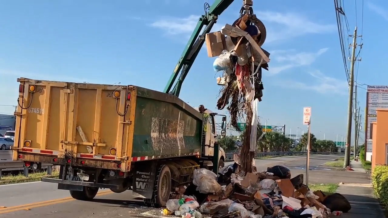 Firefighters empty piles of garbage on street to see if someone is trapped in truck
