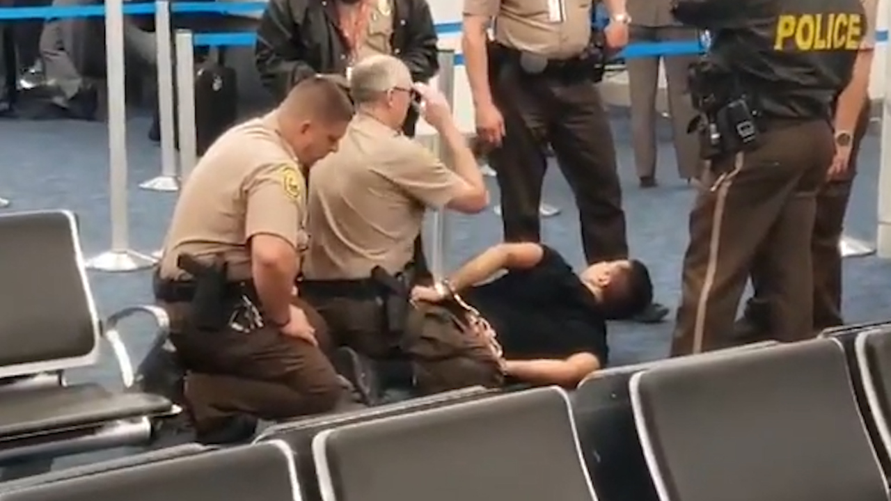 A passenger who bolted toward plane is taken into custody at Miami airport, police say