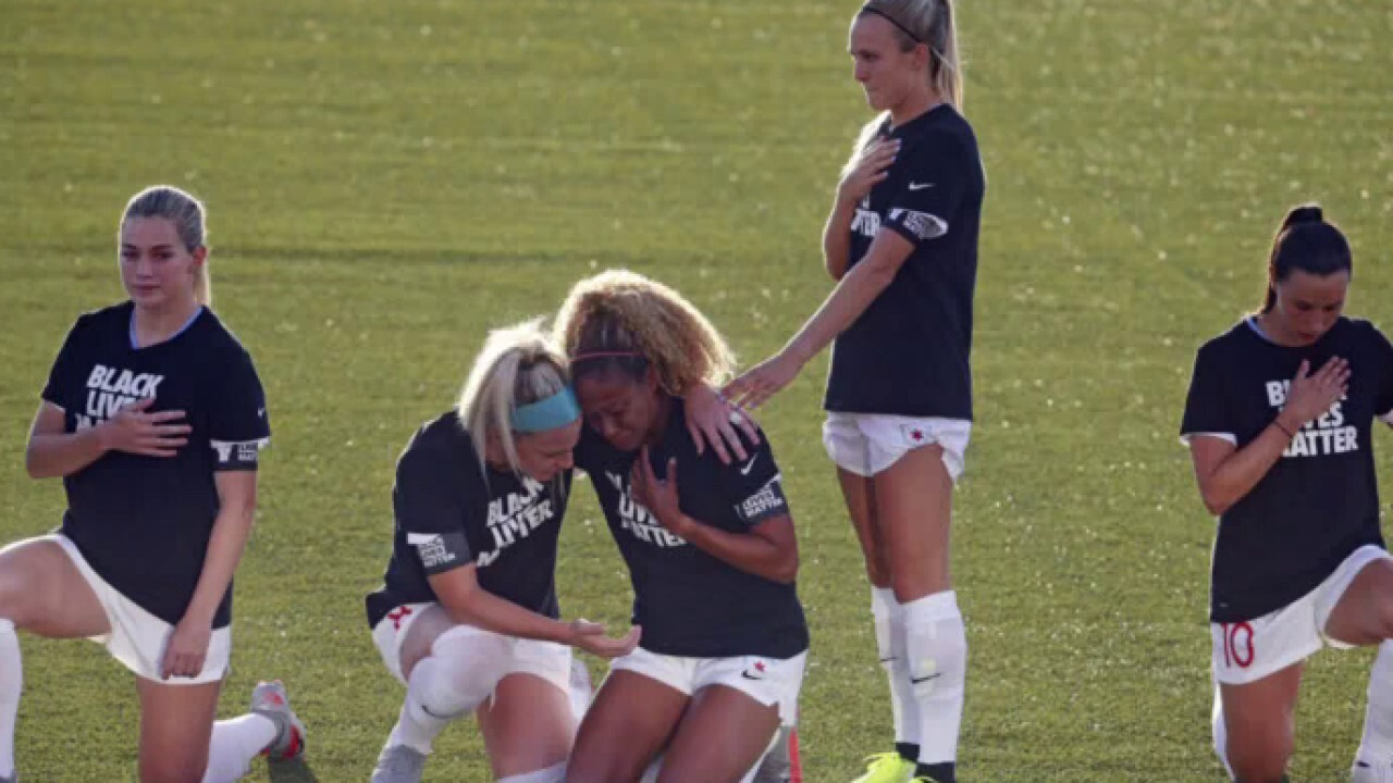 Women's soccer player stands for national anthem while teammates kneel