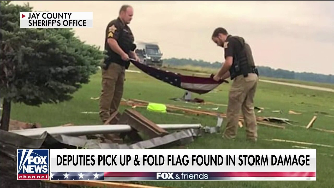 Indiana officers pick up, fold American flag found in tornado debris