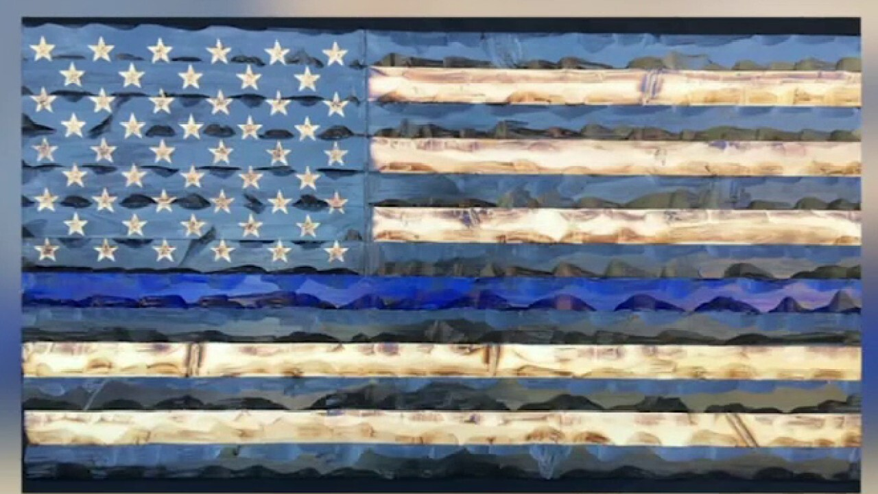 High school student raises $2,500 for veterans by making wooden American flags