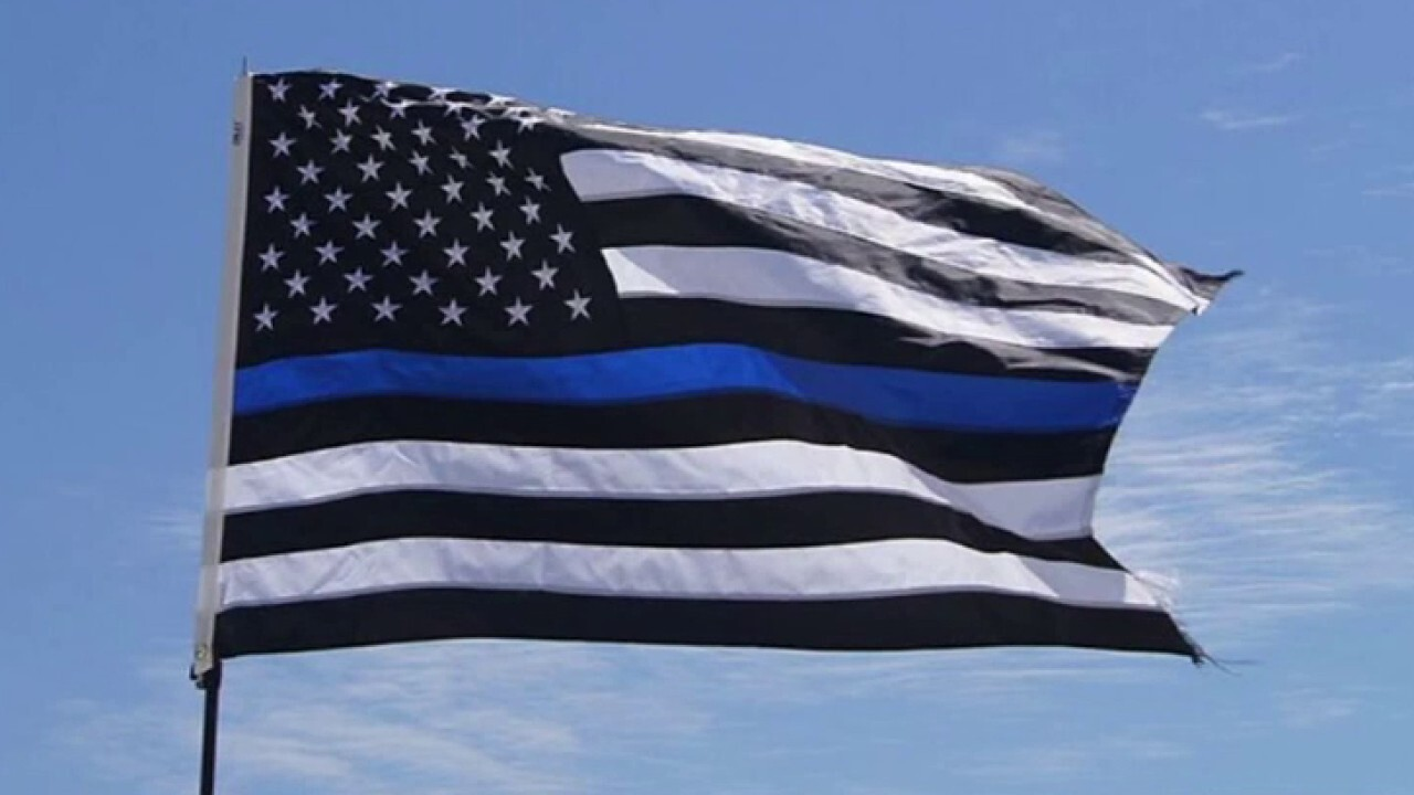 School district restricts Thin Blue Line flags after football players carried one to honor coach