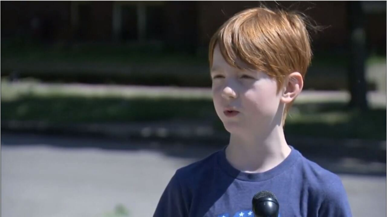 9-year-old holds homemade signs outside house to protest for George Floyd