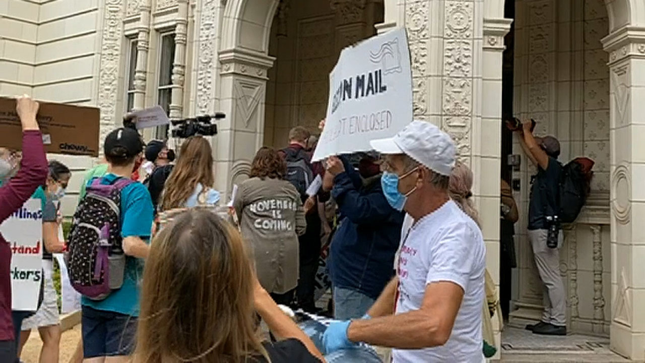 Protesters with signs and noisemakers set upon the Postmaster General's home