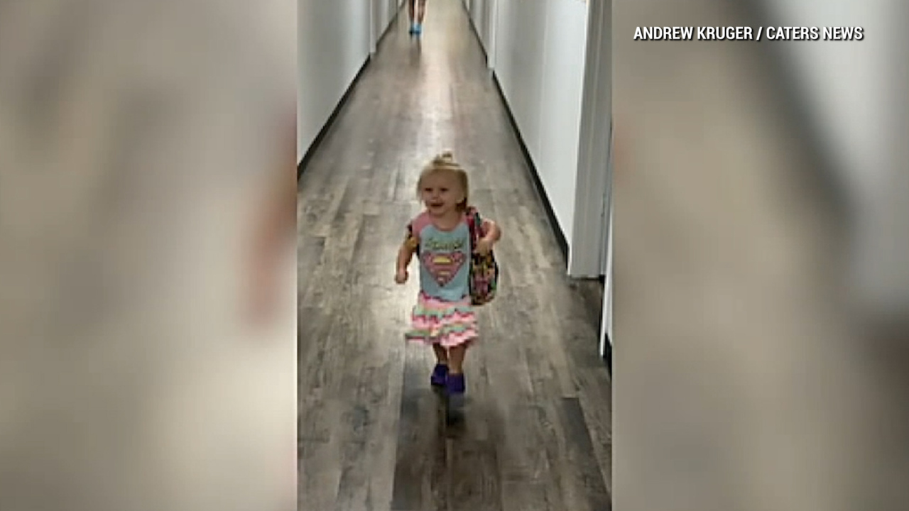 Excited toddler falls while running to greet dad after school