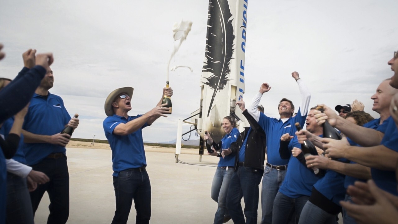 Blue Origin founder Jeff Bezos and three passengers react to the historic launch aboard the New Shepard.
